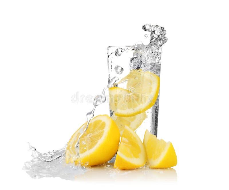 Neue Scheibe der Zitrone fallend in Glas mit Wasser stockfotos