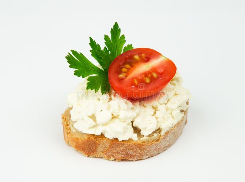 Neue Scheibe des Stangenbrotbrotes geschmiert mit Frischkäse des Häuschens mit Petersilie und Tomate lizenzfreie stockfotos