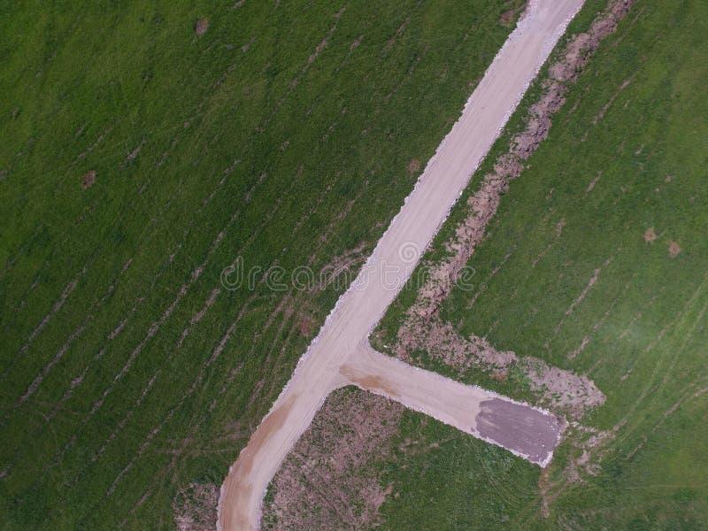 Neue Schotterstraße in der menschlichen Auswirkung des grünen Feldes zu Natur concep lizenzfreie stockfotos