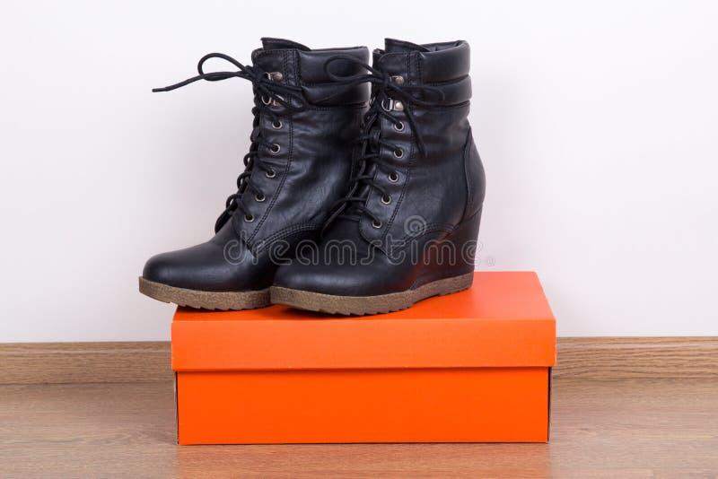 Neue schwarze weibliche Lederstiefel und Kasten lizenzfreie stockfotos