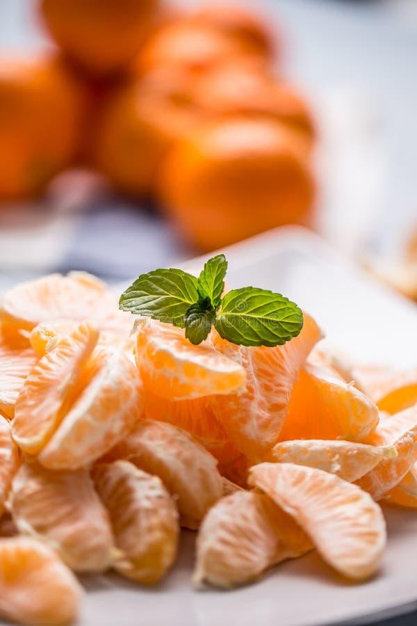 Neue Stücke der Tangerinemandarine auf der Platte oder in einer Schüssel stockbilder