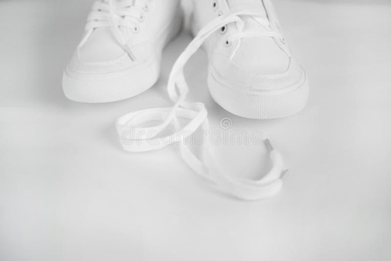 Neue weiße weibliche oder jugendlich Textilturnschuhe lokalisiert auf weißem Hintergrund Weiße Gummiturnschuhe mit gelösten Spitz stockfotografie