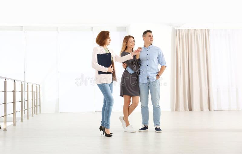 Neue Wohnung der Immobilienagenturvertretung zu den jungen Paaren stockfotografie
