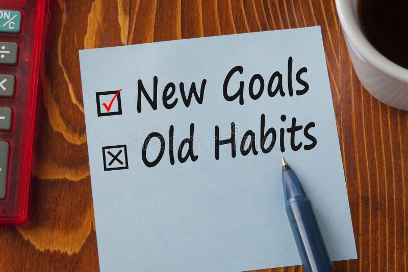 Neue Ziel-alte Gewohnheiten geschrieben auf Anmerkungskonzept lizenzfreie stockfotografie