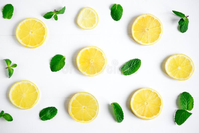 Neue Zitronenscheiben auf einem weißen Hintergrund Hintergrund mit Zitrone und Minze Schönes Foto mit Zitrusfrucht Vitamin C Zitr stockfotografie