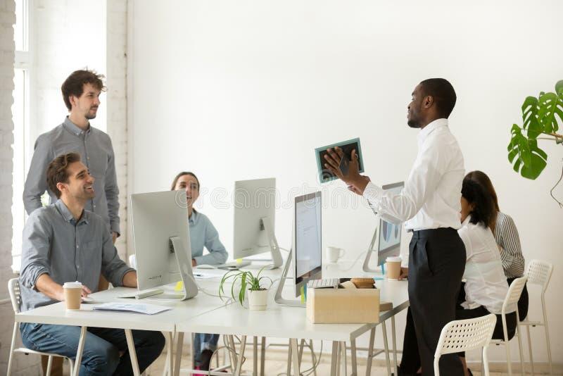 Neuer afrikanischer Angestellter, der die Unterhaltung auf dem ersten Büro Arbeits ist d auspackt lizenzfreie stockfotos