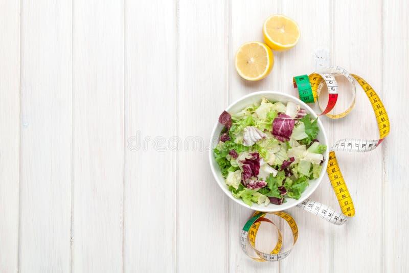Neuer gesunder Salat, Geräte und Maßband über weißem hölzernem lizenzfreie stockfotografie