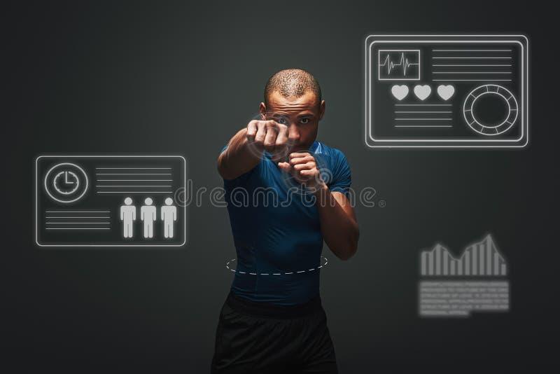 Neuer Meister Muskulöser Boxer ist bereit zu kämpfen Junge Sportlerstellung über dunklem Hintergrund Spielkonzept mit Grafik stockbilder