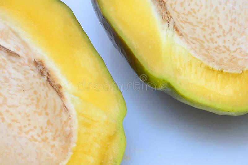 Neuer, reifer Mangoschnitt zur H?lfte Abstrakter Hintergrund mit Fragmenten der geschnittenen Frucht Konzept: gesundes Lebensmitt stockbild