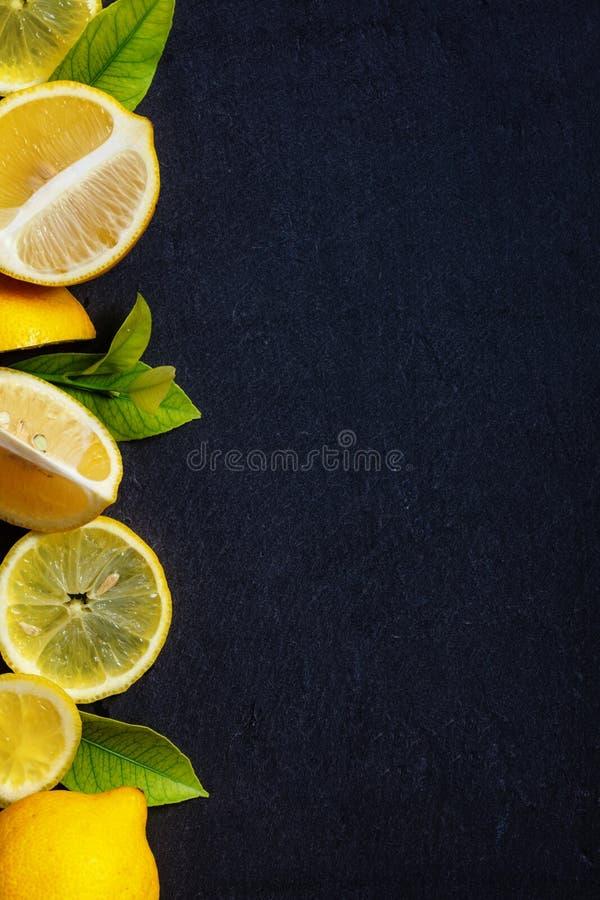 Neuer Schnitt und ganze Zitronen mit grünen Blättern auf dunkler Steintabelle lizenzfreie stockbilder