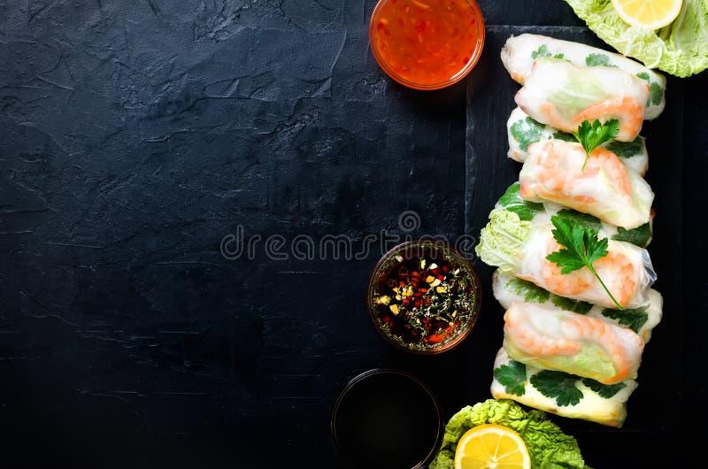 Neuer vietnamesischer, asiatischer, chinesischer Lebensmittelrahmen auf schwarzem konkretem Hintergrund Frühlingsrollenreispapier stockfotografie