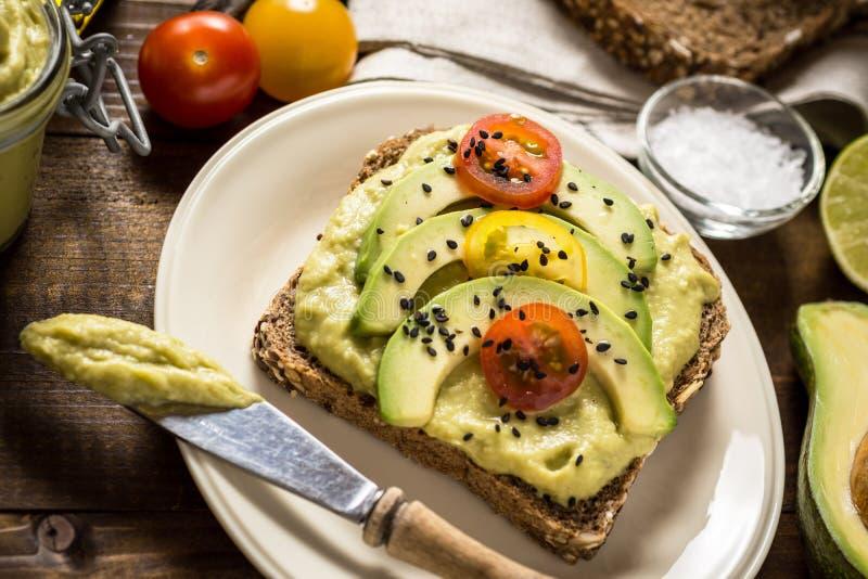 Neues Avocado-Verbreitungs-Guacamole und Scheiben mit Cherry Tomato und schwarzem indischem Sesam auf einem Stück Brot stockbild