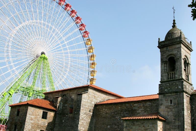 Neues buntes Riesenrad und alte spanische Kirche stockbilder
