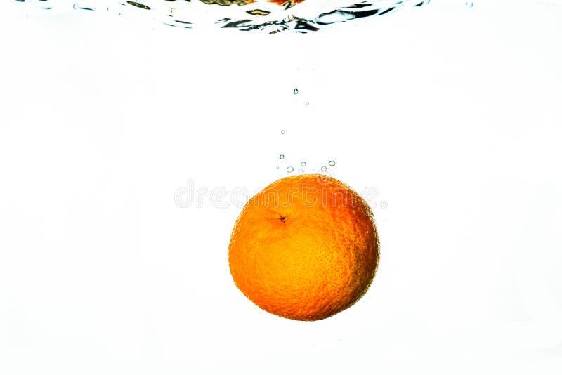 Neues friut fällt in Wasser mit Spritzen lizenzfreies stockbild