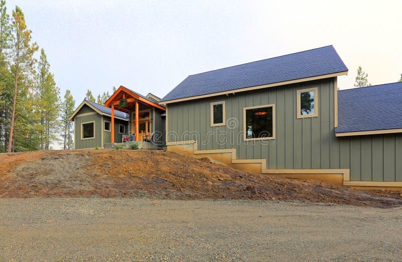 Neues graues hölzernes Landhausäußeres mit grünem Gras stockfotografie