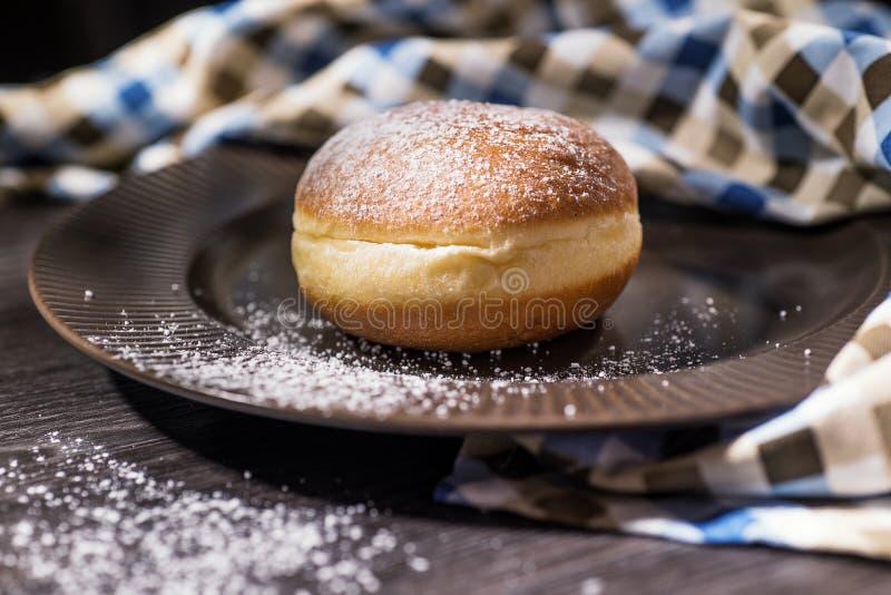 Neues Haupt-donute auf einer braunen Platte besprüht lizenzfreies stockbild
