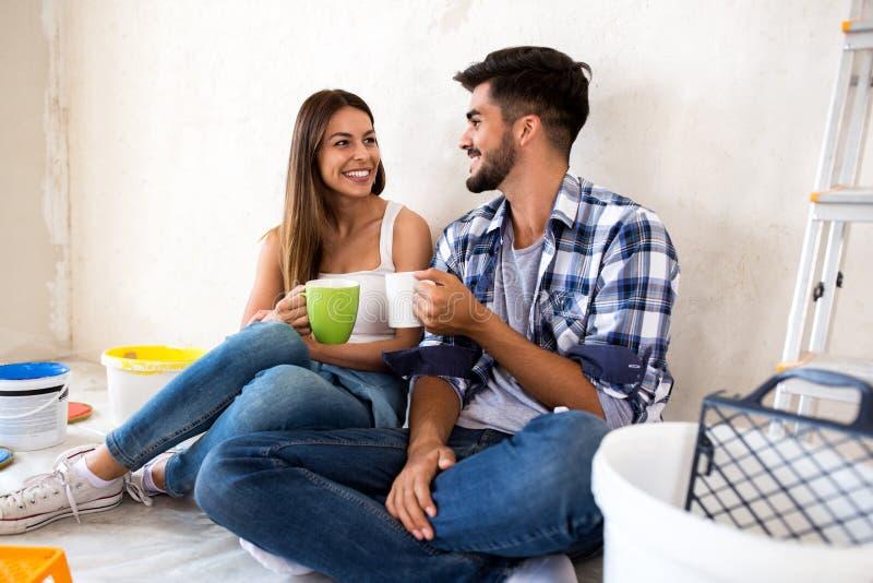 Neues Haus der glücklichen jungen Paarerneuerung lizenzfreies stockfoto