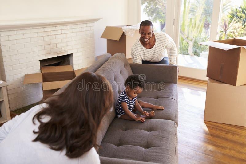 Neues Haus Eltern-Carry Son On Sofa Intos an beweglichem Tag stockfoto