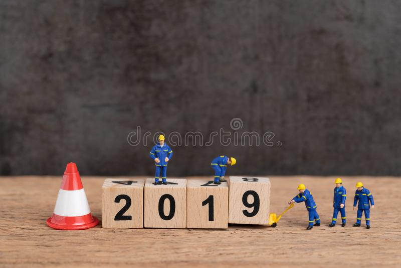Neues Jahrändern des Jahres 2019 oder gerade fertiges Konzept, Miniaturleutearbeitskräfte, die Würfelholzklotz Nr. 2019 mit darun stockfoto
