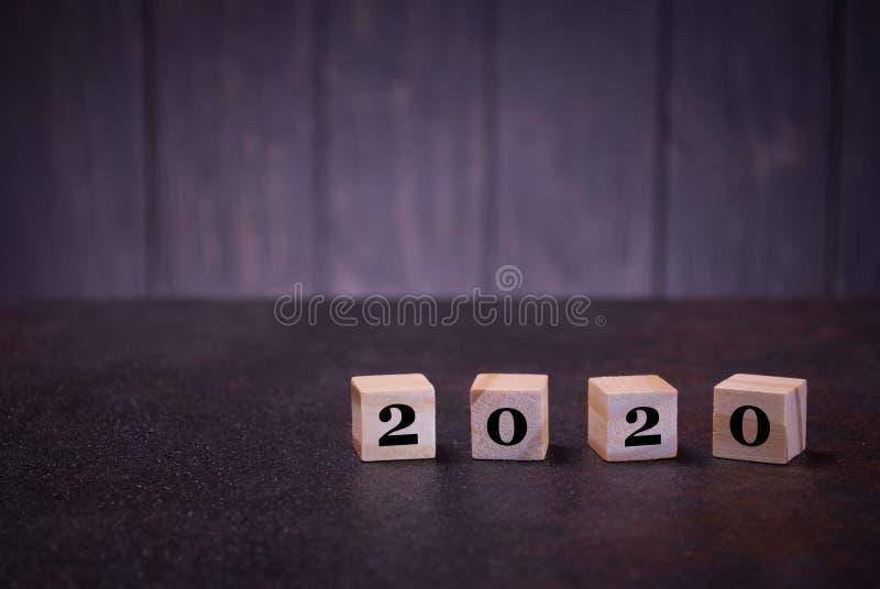 Neues Jahr der Nr.-2020 auf hölzernen Würfeln, auf einem dunklen Hintergrund, helle hölzerne Würfelzeichen lizenzfreies stockbild