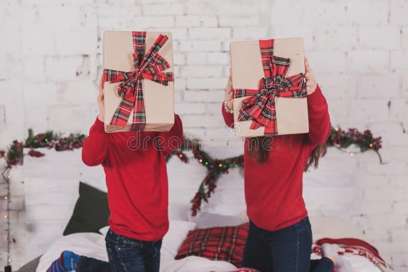 Neues Jahr des Mädchens und des Kindes mit Geschenken in den Händen lizenzfreie stockbilder