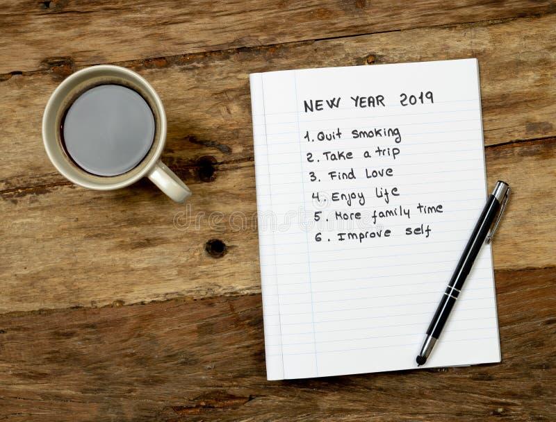 2019 neues Jahr geschrieben auf Notizbuch mit Kaffee auf hölzerner Tabelle auf Beschlüsse und Zielen für glückliches Leben lizenzfreie stockbilder