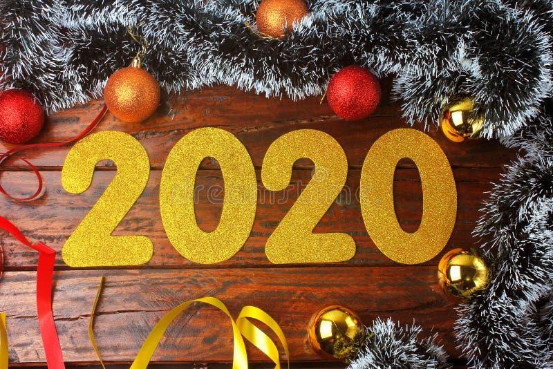 2020 neues Jahr, goldene Zahlen auf aufwändigem rustikalem Holztisch in der festlichen Feier stockfoto
