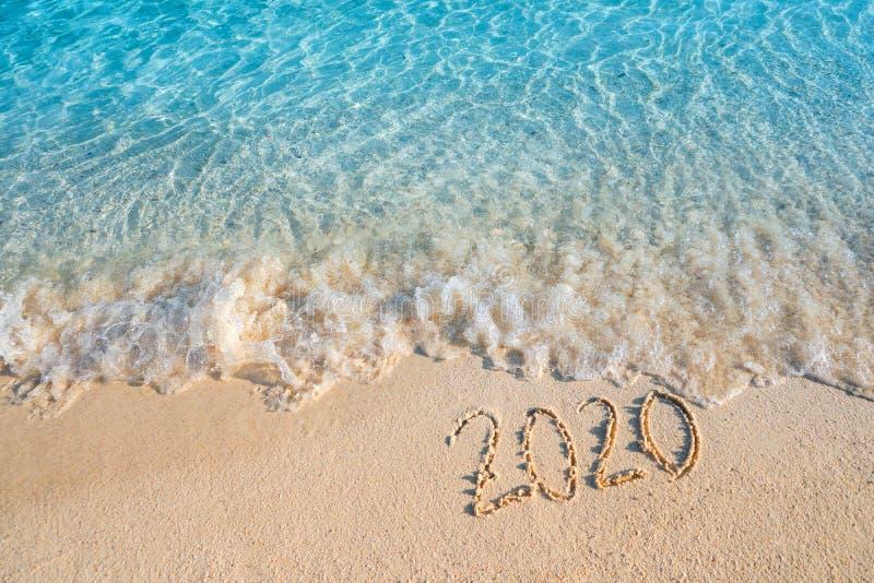Neues Jahr hüllte ein 2020-Sommer-Konzept, weiche Welle den Hintergrund des sandigen Strandes ein lizenzfreie stockfotos