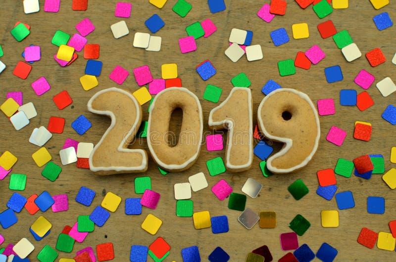Neues Jahr 2019 Lebkuchenzahlen auf einem hölzernen Brett Grüße des neuen Jahres Passend als Hintergrund Bunte Paillette stockbild