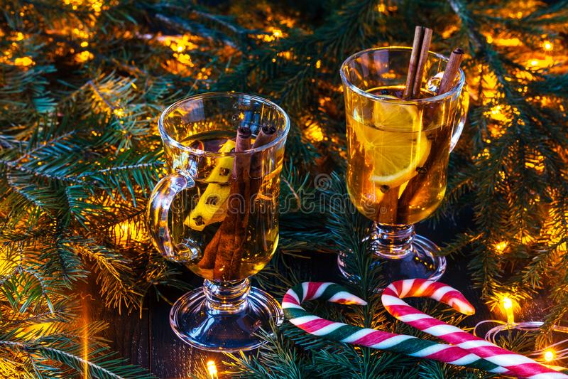 Neues Jahr ` s Glühwein in einem Glas auf dem Hintergrund von Zweigen, von Kerzen und von Girlanden lizenzfreies stockbild
