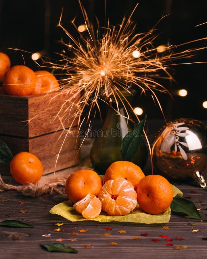 Neues Jahr `s Konzept Tangerinen in einer Holzkiste Wunderkerze brennt in einem Vase stockfotografie