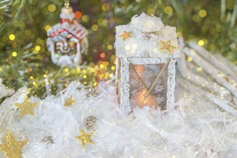 Neues Jahr ` s, Weihnachtsstillleben Weihnachtshandgemachte verzierte Laterne im Schnee mit Gold spielt auf grünem Tannenbaumhint stockbild