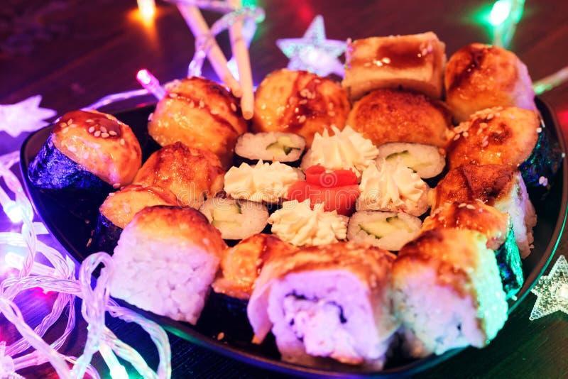 Neues Jahr-Sushi Schönes Nahrungsmittelfoto mit Weihnachtsgirlande lizenzfreie stockfotos