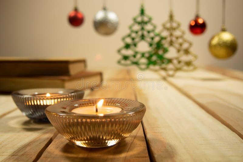 Neues Jahr und Weihnachtszusammensetzungshintergrund mit Aromakerze, Büchern und dem Dekoration Weihnachtsball auf dem Tisch hölz stockbild