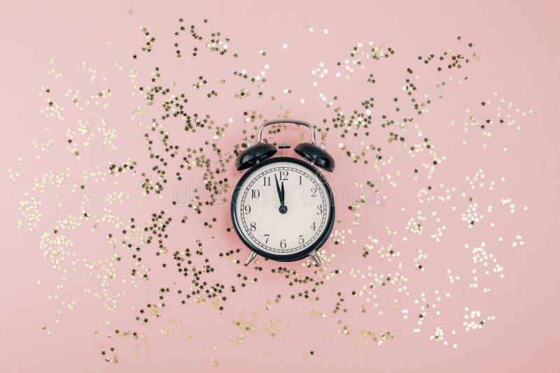 Neues Jahr-Weihnachtsdraufsicht legen flach schwarzen Wecker zwölf bedeckte tausendjähriges rosa Papier des goldenen Sternkonfett stockfotografie