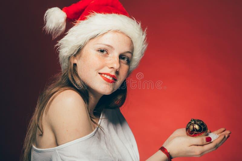 Neues Jahr-Weihnachtskappen-Frauenporträt auf rotem Hintergrund lizenzfreie stockfotos