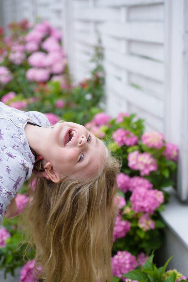 Neues Leben-Konzept Frühlingsfeiertag Sommer Mutter- oder Frauentag Wenig Mädchen an blühender Blume Gerade ein geregnet lizenzfreies stockfoto