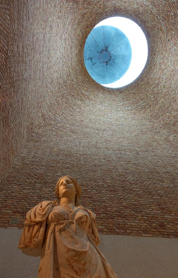 Neues Museum Berlin with a Classic Female Statue and Oculus. A classic sculpture of a Goddess in the Light Room of the Neues Museum in Berlin, Germany. The room stock photography