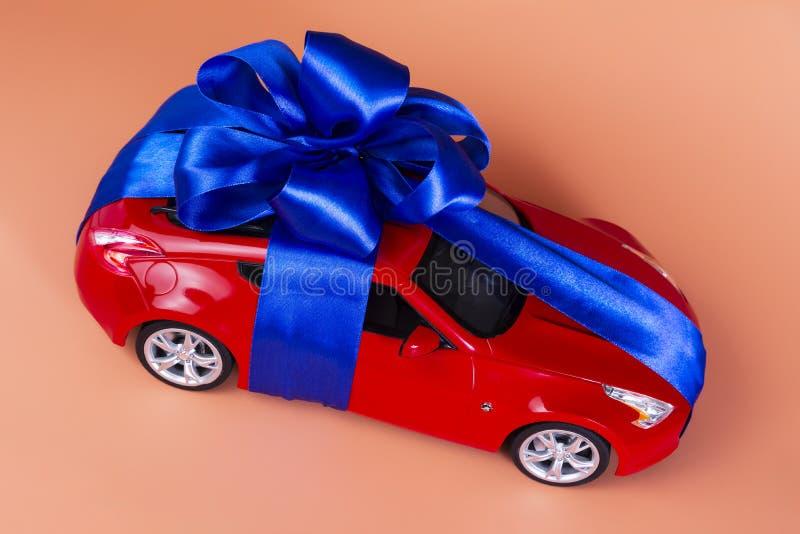 Neues rotes Auto mit einem blauen Bogen als Geschenk auf einem korallenroten Hintergrund lizenzfreies stockbild