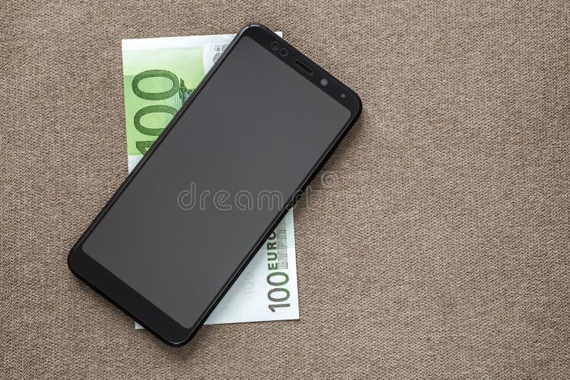 Neues schwarzes modernes digitales Mobiltelefon auf Geldeurobanknote auf Kopienraum-Beschaffenheitshintergrund Moderne Technologi lizenzfreies stockfoto