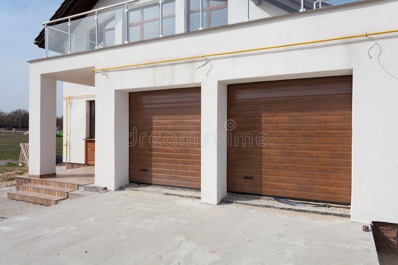 Neues weißes Haus mit Doppelgaragetüren und -balkon stockfotografie