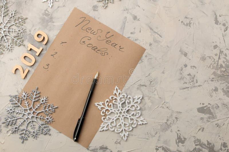 An neuf Buts pour 2019 texte sur un morceau de papier avec des flocons de neige et stylo sur un fond clair images libres de droits