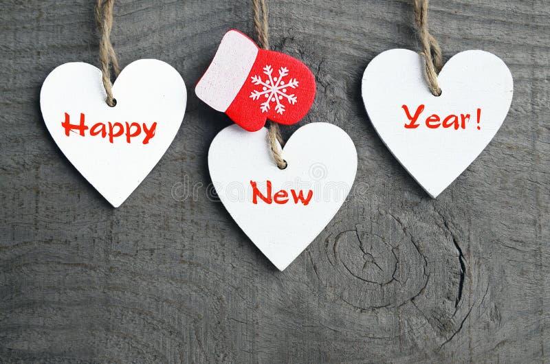 An neuf heureux Coeurs en bois blancs décoratifs de Noël et mitaines rouges sur le fond en bois Concept de vacances d'hiver image stock