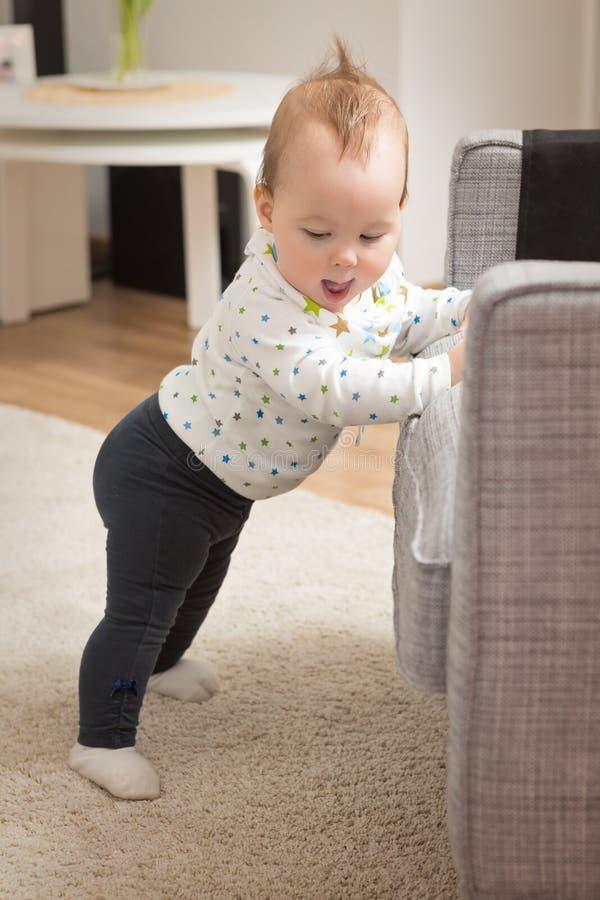Neuf mois de bébé se tenant sur ses pieds photographie stock