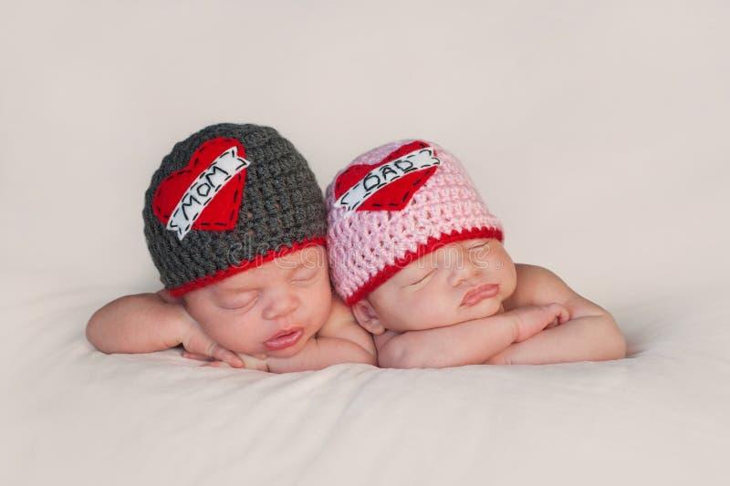 Neugeborene Baby-Zwillinge in den Liebes-Mutter-und Vati-Hüten lizenzfreie stockbilder
