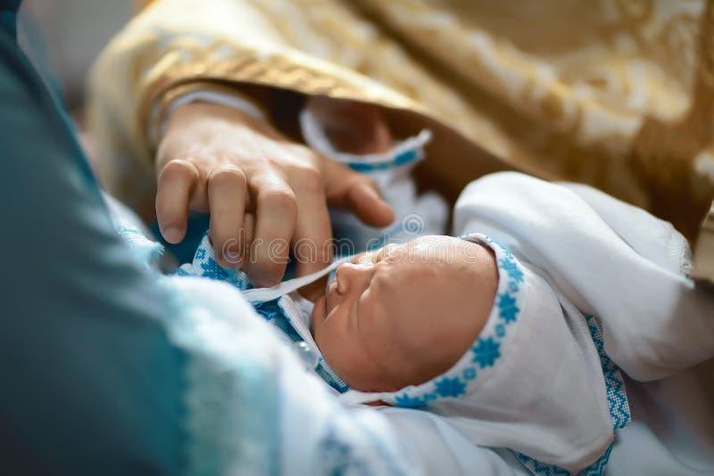 Neugeborene Babytaufe durch Öl mit den Händen des Priesters lizenzfreies stockfoto