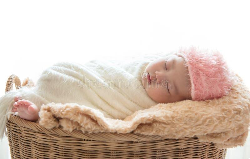 Neugeborener Babyschlaf auf seinem braunen Korb, der unter einem Whit sich entspannt lizenzfreies stockfoto