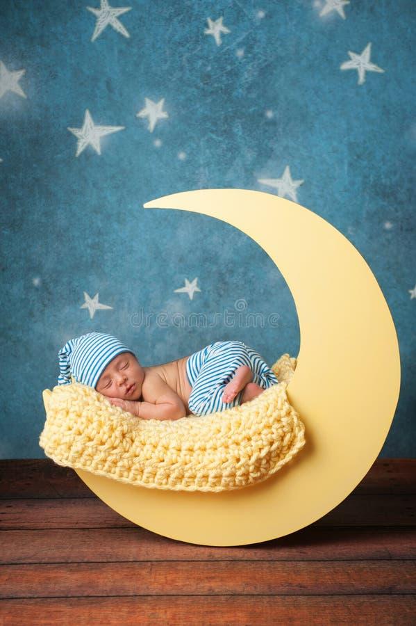 Neugeborener Junge, der auf dem Mond schläft lizenzfreie stockfotos
