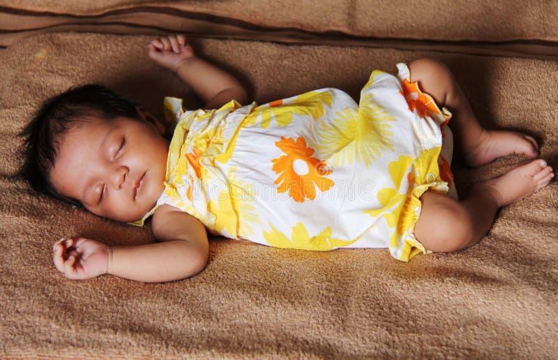 Neugeborenes asiatisches Baby, das im netten Kleid schläft lizenzfreies stockbild