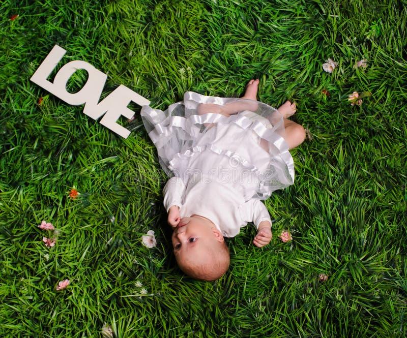 neugeborenes Baby auf einem grünen Gras lizenzfreies stockbild